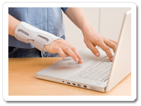A woman with a wrist brace on while using a laptop